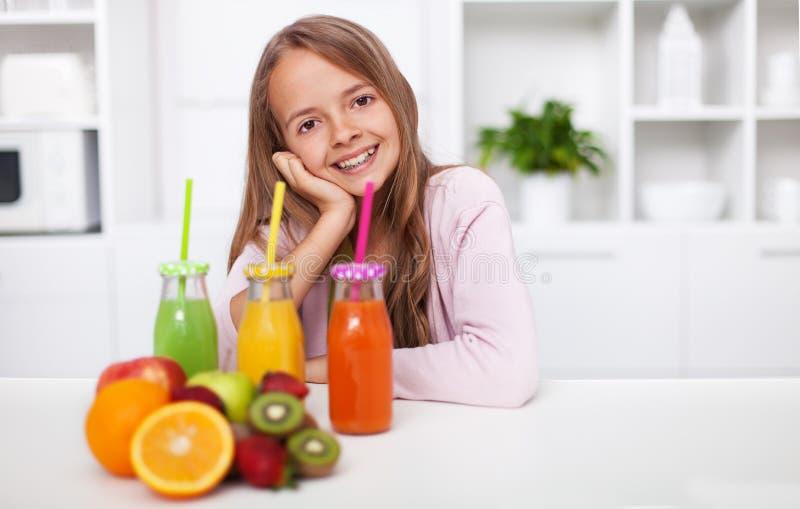Jeune fille d'adolescent préparant le jus de fruit frais dans la cuisine photo stock