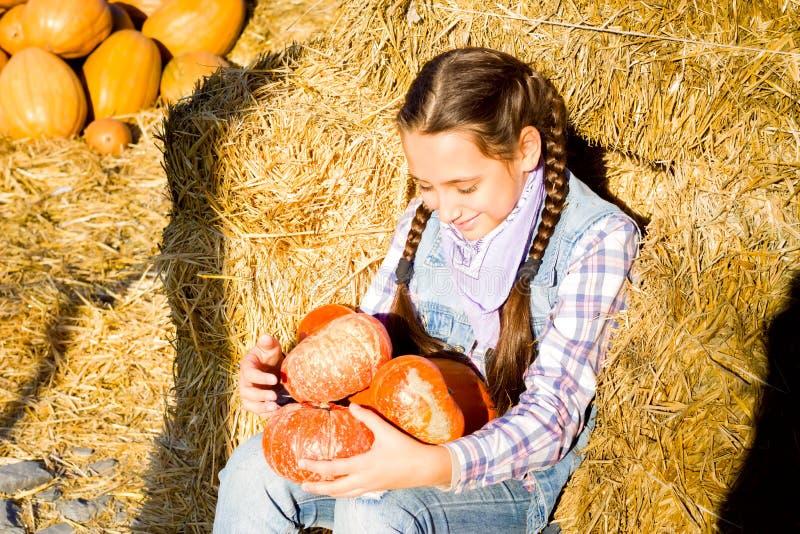 Jeune fille d'adolescent s'asseyant sur la paille avec des pumkins sur le marché de ferme Famille célébrant le thanksgiving ou le photographie stock libre de droits