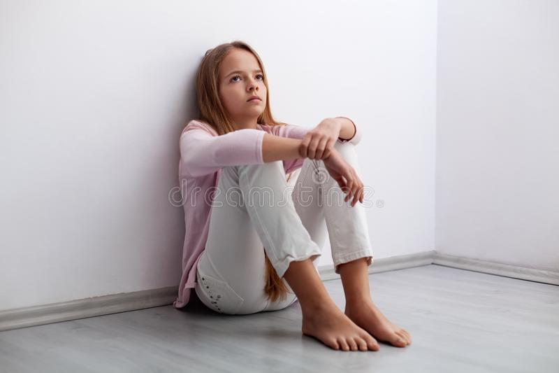 Jeune fille d'adolescent s'asseyant sur le plancher par le mur - regard d'a images libres de droits