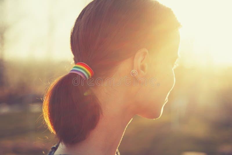 Jeune fille d'arrière avec le ruban d'arc-en-ciel de LGBT dans ses cheveux dans la queue de cheval image libre de droits
