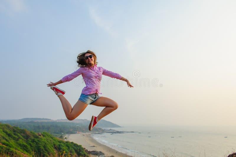 Jeune fille dans des shorts courts et des sauts roses de chemise insouciants sur une colline contre la mer Image de mode de vie d photo stock