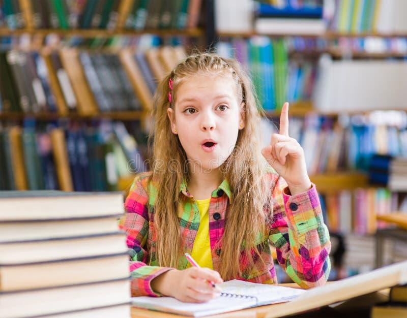 Jeune fille dans la bibliothèque montrant le doigt  image stock