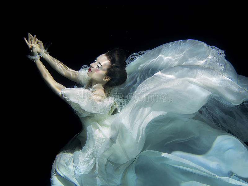 Jeune fille dans la longue robe blanche sous-marine images stock
