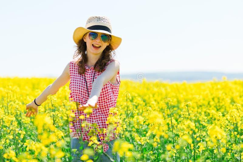Jeune fille dans la robe à carreaux rouge et chapeau de soleil posant dans le domaine de colza oléagineux photographie stock libre de droits