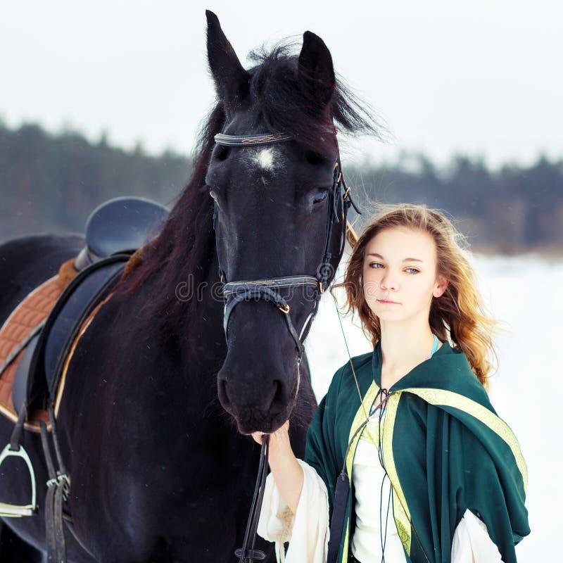 Jeune fille dans la robe avec le cheval noir en hiver image libre de droits