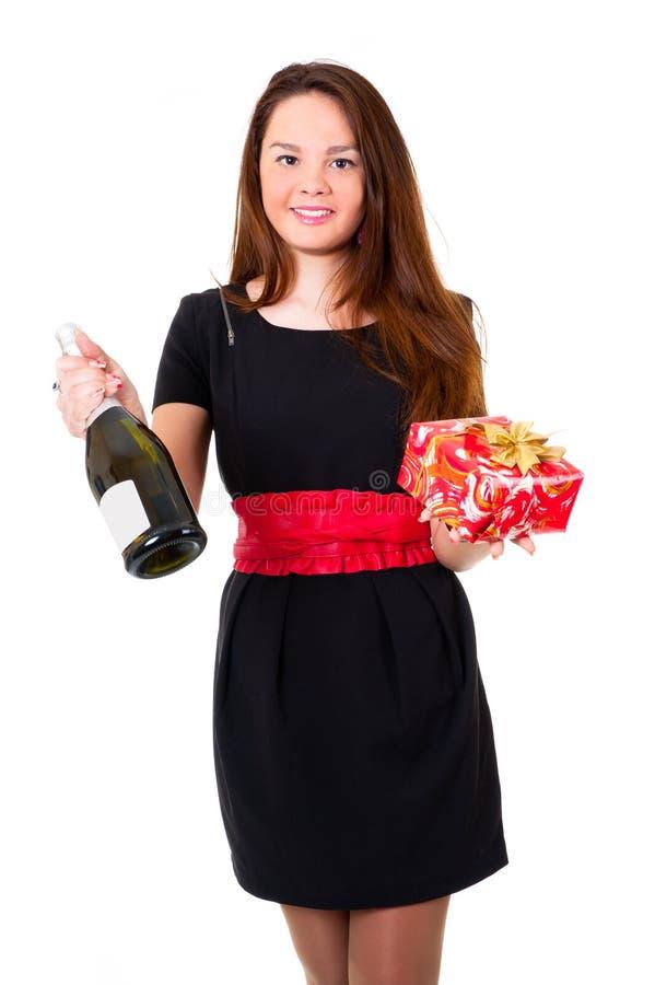 Jeune fille dans la robe noire retenant un cadeau photos stock