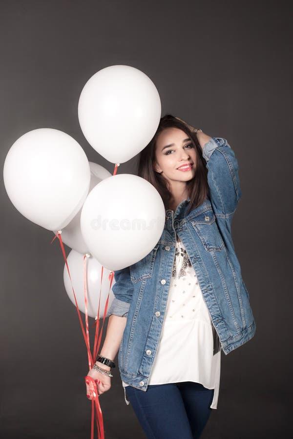 Jeune fille dans la veste de denim avec les ballons blancs photo stock