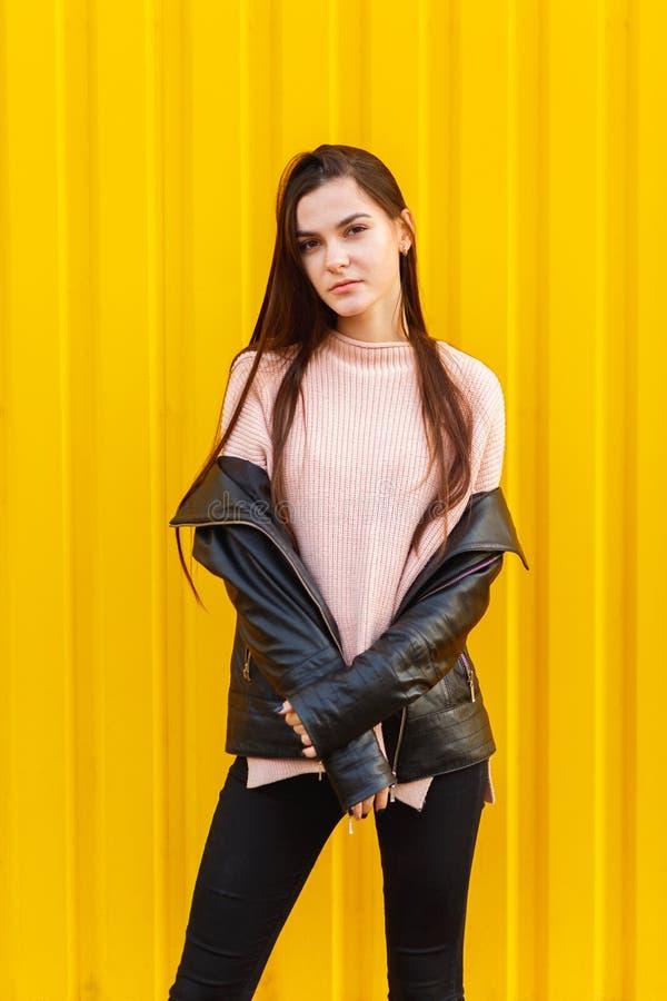 Jeune fille dans la veste posant contre le mur de corpus images stock