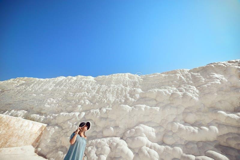 Jeune fille dans le chapeau regardant sur des piscines et des terrasses de travertin dans Pamukkale Ch?teau de coton en Turquie d images libres de droits