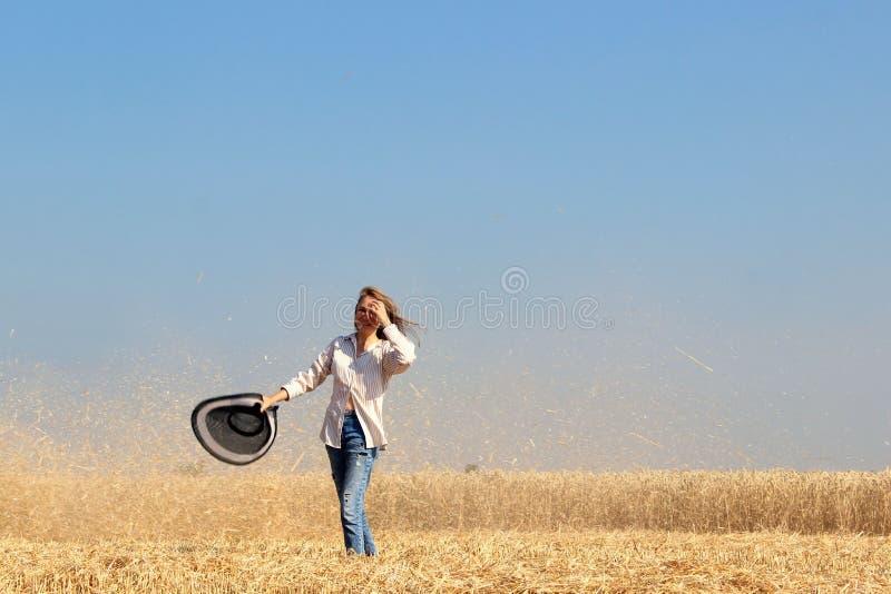 Jeune fille dans le domaine Les gens, moissonnant le concept Jeune fille marchant sur un champ de blé au-dessus de fond de ciel b photographie stock libre de droits