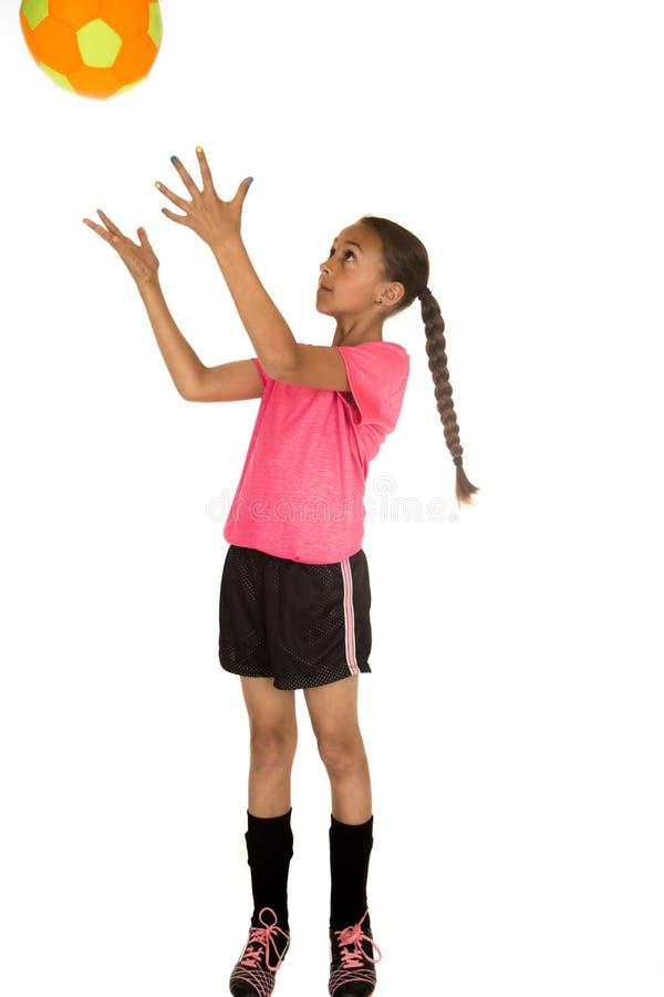 Jeune fille dans le football uniforme attrapant un ballon de football photo libre de droits
