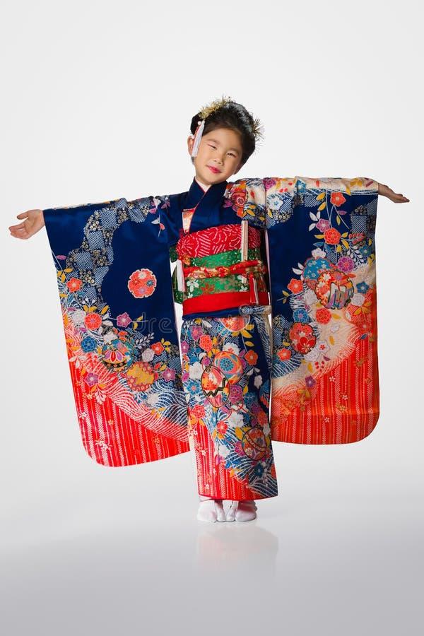Jeune fille dans le kimono sur le blanc image stock