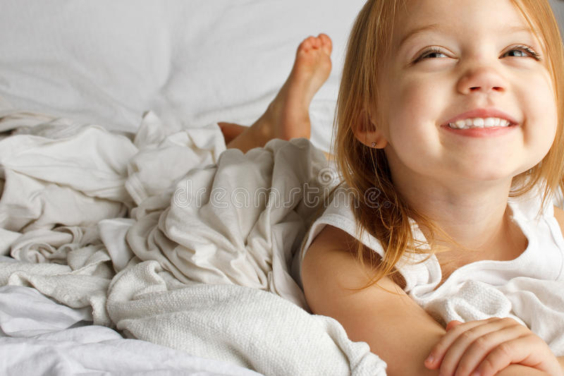 Jeune fille dans le lit couvert blanc image stock