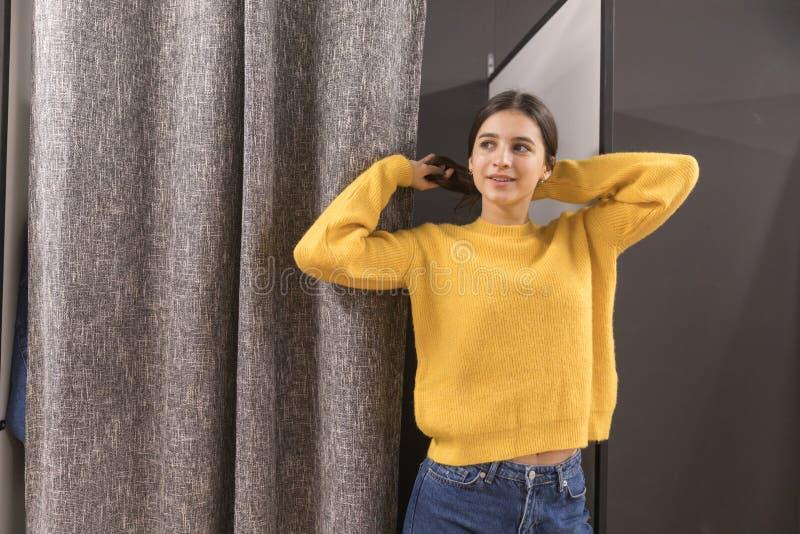 Jeune fille dans le magasin d'habillement essayant sur un chandail jaune image stock