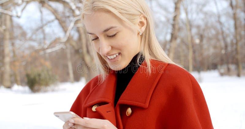 Jeune fille dans le manteau rouge d'hiver utilisant le téléphone portable en parc de ville images stock