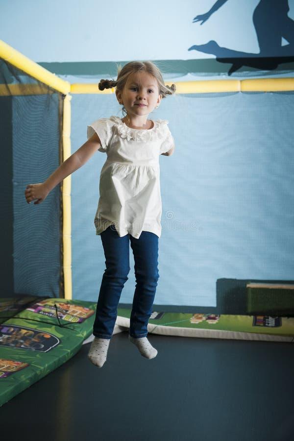 Jeune fille dans le plein vol sur le trempoline photographie stock libre de droits
