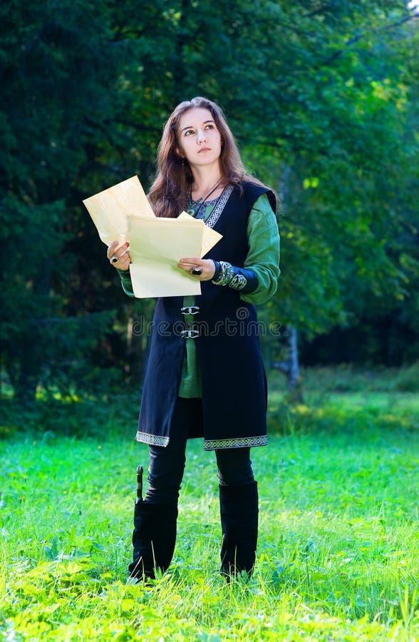 Jeune fille dans le procès médiéval avec de vieux papiers image stock