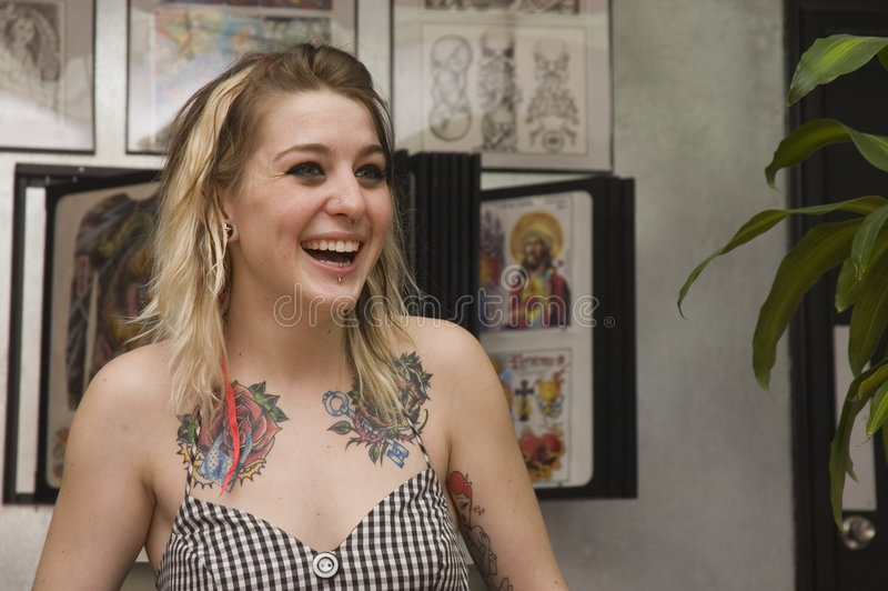 Jeune fille dans le salon de tatouage photo stock
