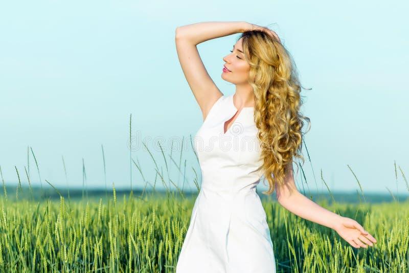 Jeune fille dans un domaine de blé appréciant la nature de jour ensoleillé images libres de droits