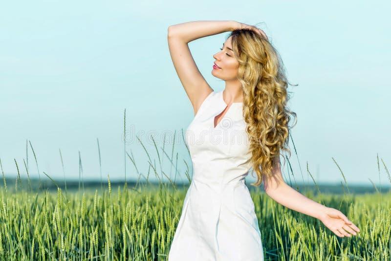 Jeune fille dans un domaine de blé appréciant la nature de jour ensoleillé photo libre de droits