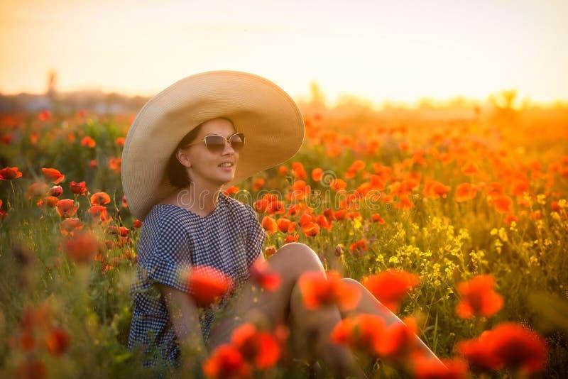 Jeune fille dans un grand chapeau se reposant sur un champ de pavot dans le coucher du soleil photographie stock libre de droits
