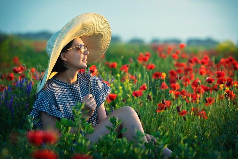 Jeune fille dans un grand chapeau se reposant sur un champ de pavot dans le coucher du soleil photo stock