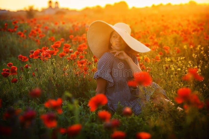 Jeune fille dans un grand chapeau se reposant sur un champ de pavot dans le coucher du soleil photos libres de droits