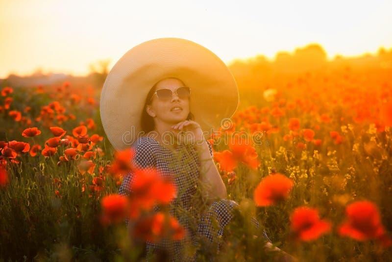 Jeune fille dans un grand chapeau se reposant sur un champ de pavot dans le coucher du soleil photo libre de droits