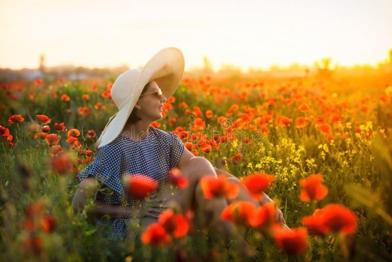 Jeune fille dans un grand chapeau se reposant sur un champ de pavot dans le coucher du soleil photographie stock