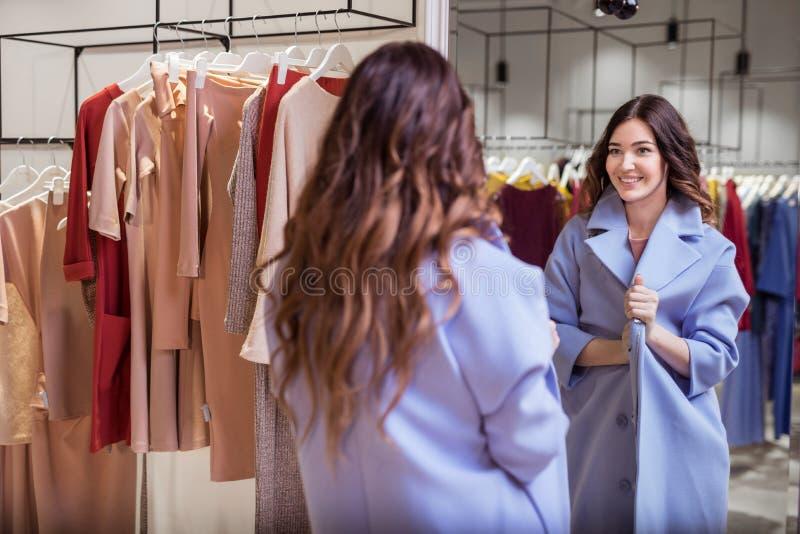 Jeune fille dans un manteau au miroir photos stock