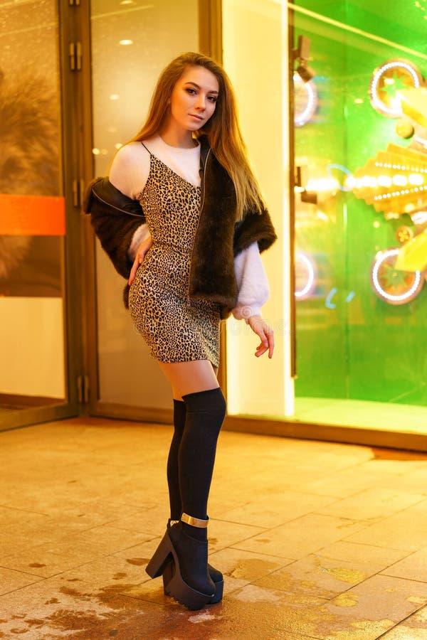 Jeune fille dans un manteau de fourrure posant pour l'humeur de fête de caméra photo libre de droits