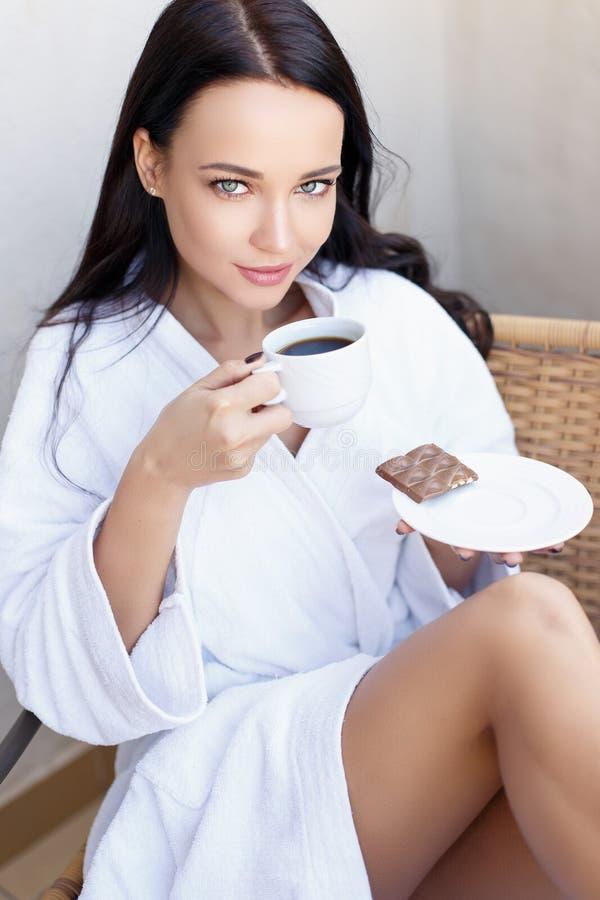 Jeune fille dans un peignoir blanc avec la tasse de café photo stock