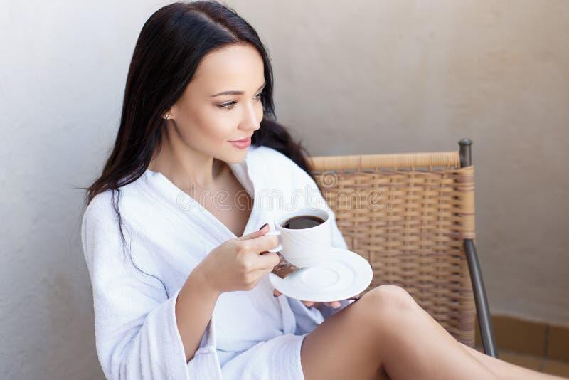 Jeune fille dans un peignoir blanc avec la tasse de café images stock