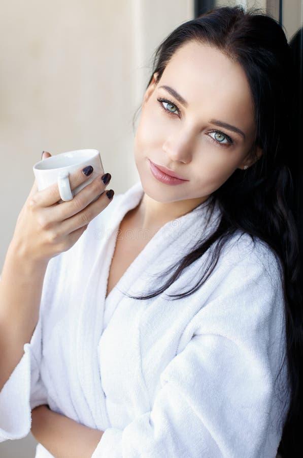 Jeune fille dans un peignoir blanc avec la tasse de café photographie stock