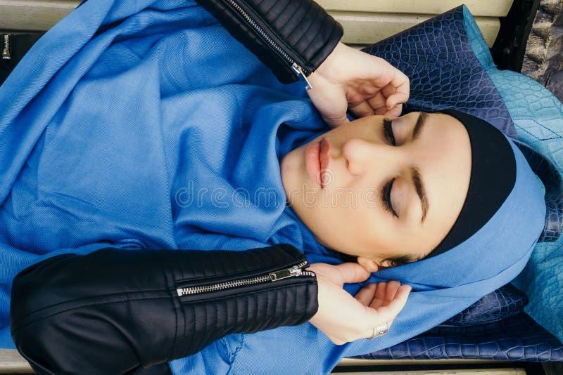 Jeune fille dans une écharpe bleue se trouvant sur le banc de parc Vue supérieure Configuration plate photos libres de droits