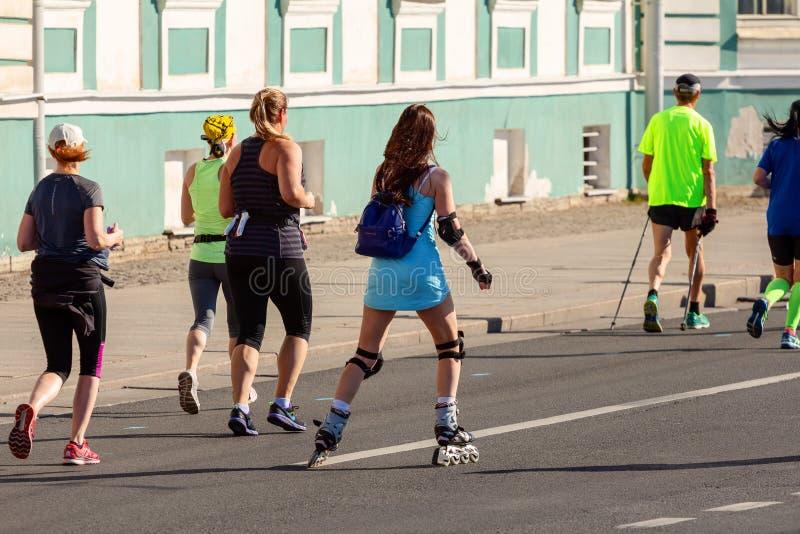 Jeune fille dans une robe courte bleue sur des tours de rouleaux le long de la rue pendant un marathon à côté des coureurs photo stock