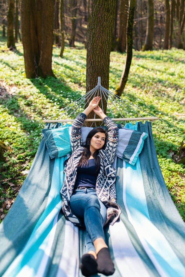Jeune fille de beatifull dans l'hamac appréciant le week-end ensoleillé quelque part au printemps en bois photos stock