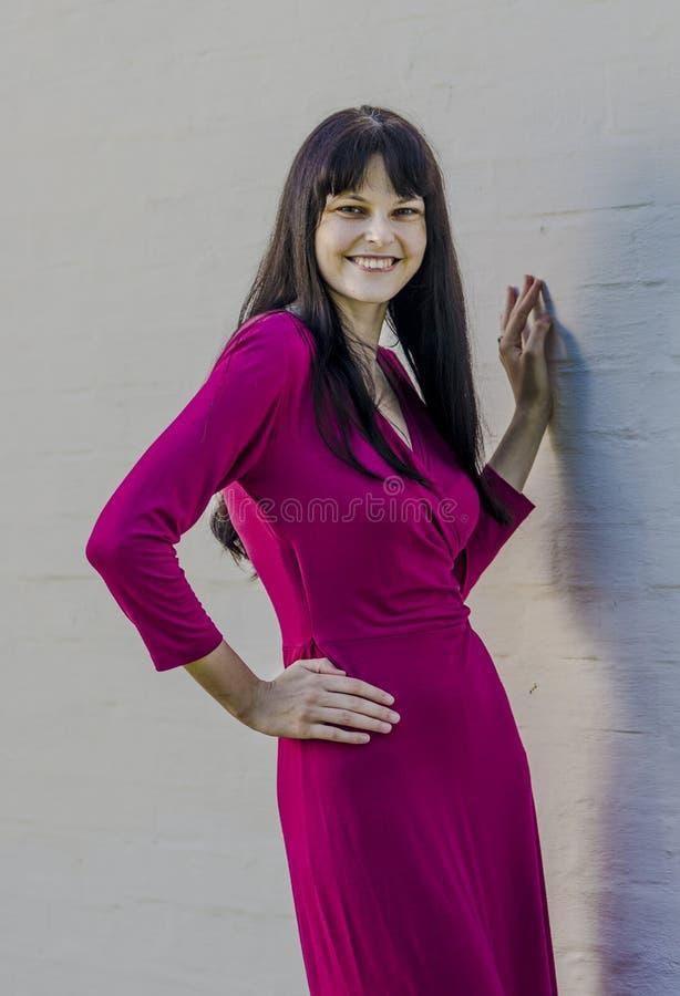 Jeune fille de brune avec des taches de rousseur dans la robe rouge dans le jardin d'été photographie stock