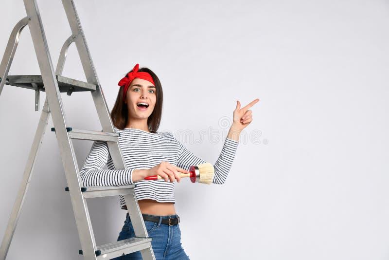 Jeune fille de brune avec une brosse et une échelle - indique un espace pour votre publicité image libre de droits