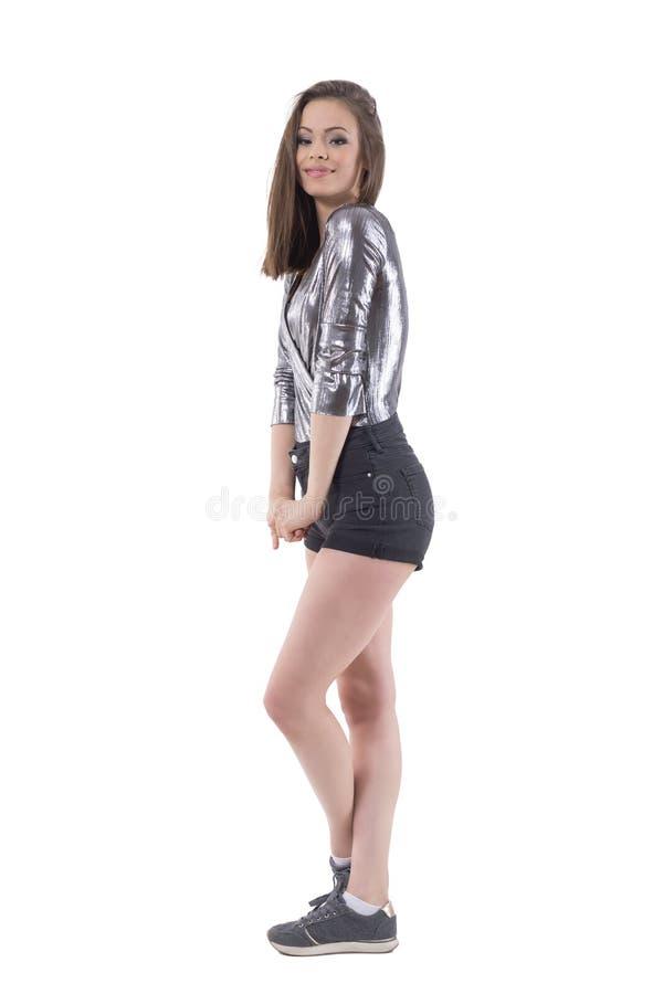 Jeune fille de brune de beauté renversante posant et regardant l'appareil-photo Vue de côté images stock
