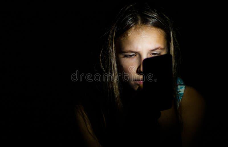 Jeune fille de brune d'adolescent à l'aide du téléphone portable dans la chambre noire sur le fond noir image stock
