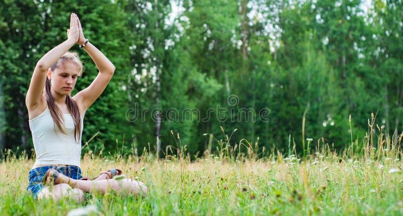Jeune fille de brune d'adolescent avec du yoga de pratique de longs cheveux sur l'herbe en parc images stock