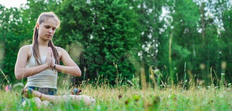 Jeune fille de brune d'adolescent avec du yoga de pratique de longs cheveux sur l'herbe en parc photo stock