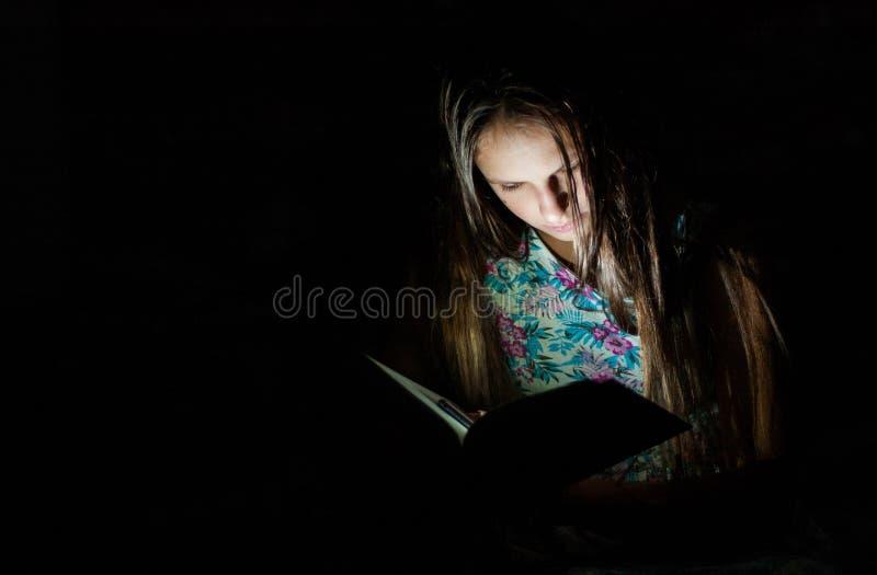 Jeune fille de brune d'adolescent lisant un livre dans une chambre noire sur le fond noir Avec l'espace de copie images stock