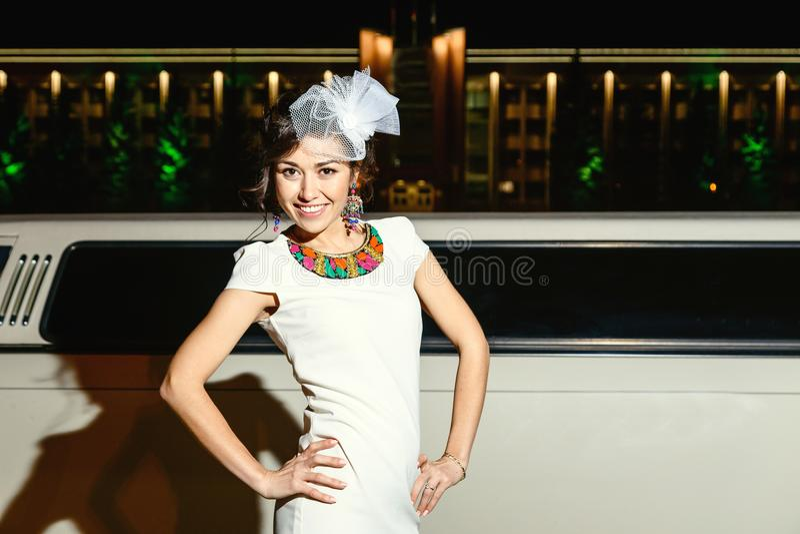 Jeune fille de brune dans la robe et le chapeau blancs à côté de la limousine blanche image stock