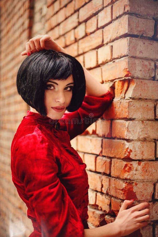 Jeune fille de brune dans la robe rouge romantique de vintage près du mur photo stock