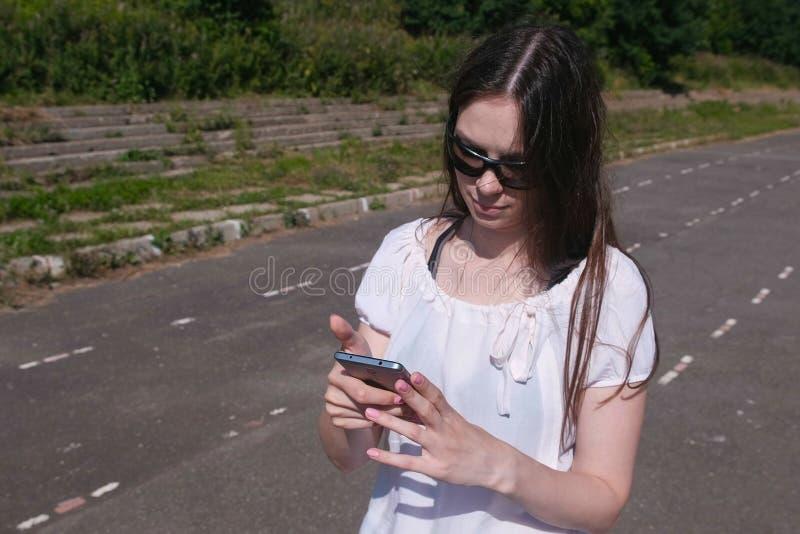 Jeune fille de brune marchant dans le stade dans une zone résidentielle et une transmission de messages à un téléphone portable images stock