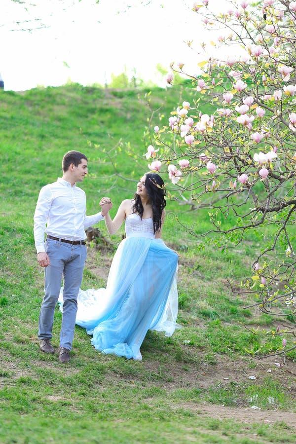 Jeune fille de brune portant la robe bleue et marchant près de la magnolia avec l'ami photo libre de droits