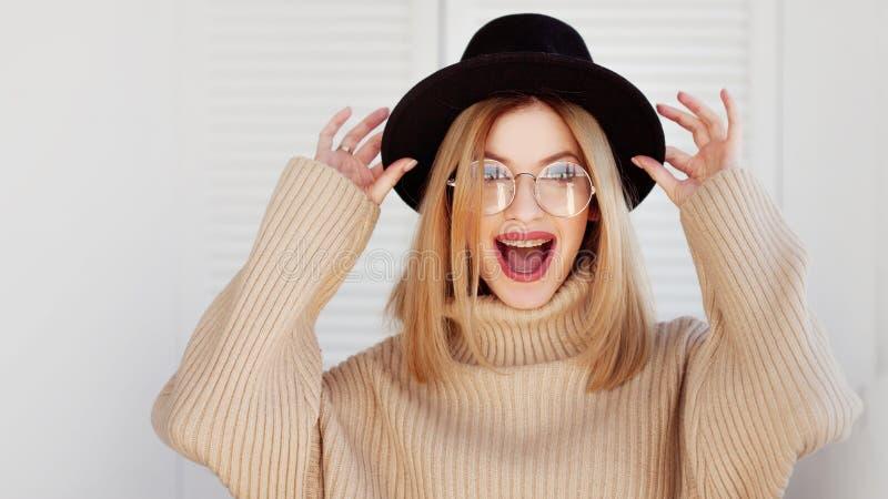 Jeune fille de charme en chapeau élégant et verres Accolades de port et sourire de jeune femme photographie stock