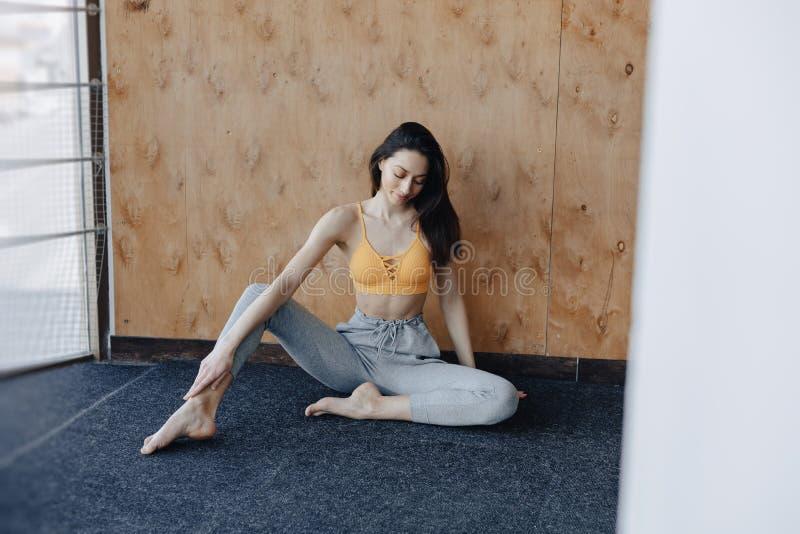 Jeune fille de fitness attirante assise sur le sol près de la fenêtre sur le fond d'un mur en bois, reposant sur des cours de yog photographie stock